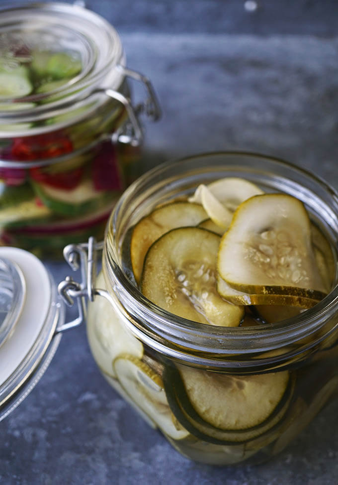 Two clear glass jars filled with refrigerator pickles on a metal serving tray.
