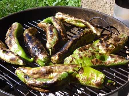 Chiles cooking on the grill. Their skin is blistered and bubbly.