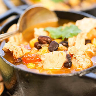 Slow Cooker Chicken Taco Soup is a cast iron bowl with spoon.