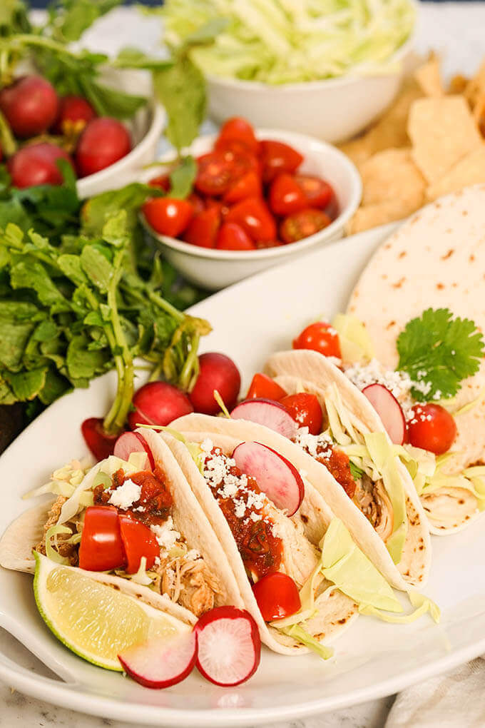 A white platter filled with slow cooker chicken tacos on flour tortillas topped with cabbage, tomatoes and sliced radishes.