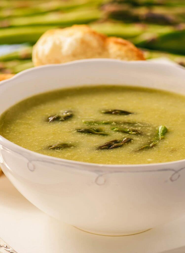 Vegetarian asparagus soup in white bowl serve with fresh homemade rolls.