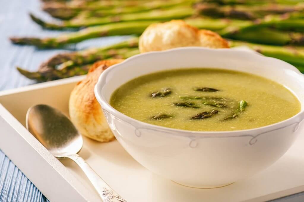 Soup on platter served with rolls and asparagus on the side.