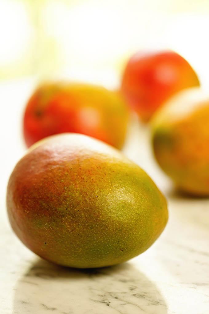 Juicy ripe mangos on a white marble slab