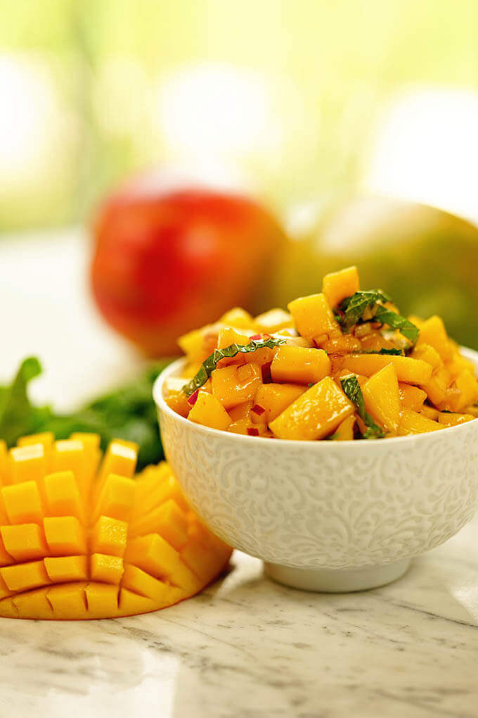 Mango salsa in a white bowl surrounded by fresh sliced mango and mint.