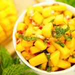 A bowl of mango salsa recipe surrounded by mint and fresh sliced mango.