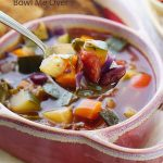 A spoonful of the best minestrone soup recipe. There's a red bowl in the background filled with more minestrone soup.