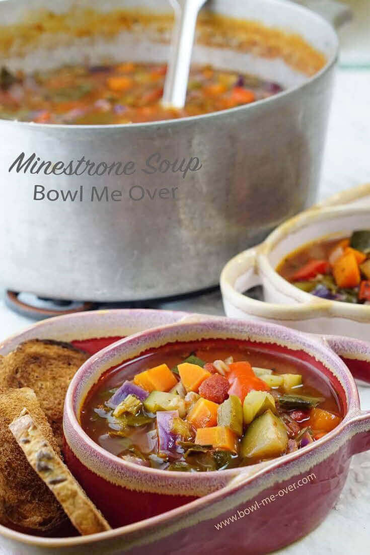 Two bowls full of Minestrone Soup. Each bowl has a serving of crackers. In the background is an stockpot filled with steaming Minestrone Soup
