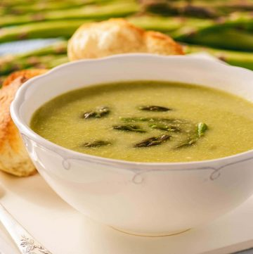 Creamy Soup in white bowl topped with asparagus spears.