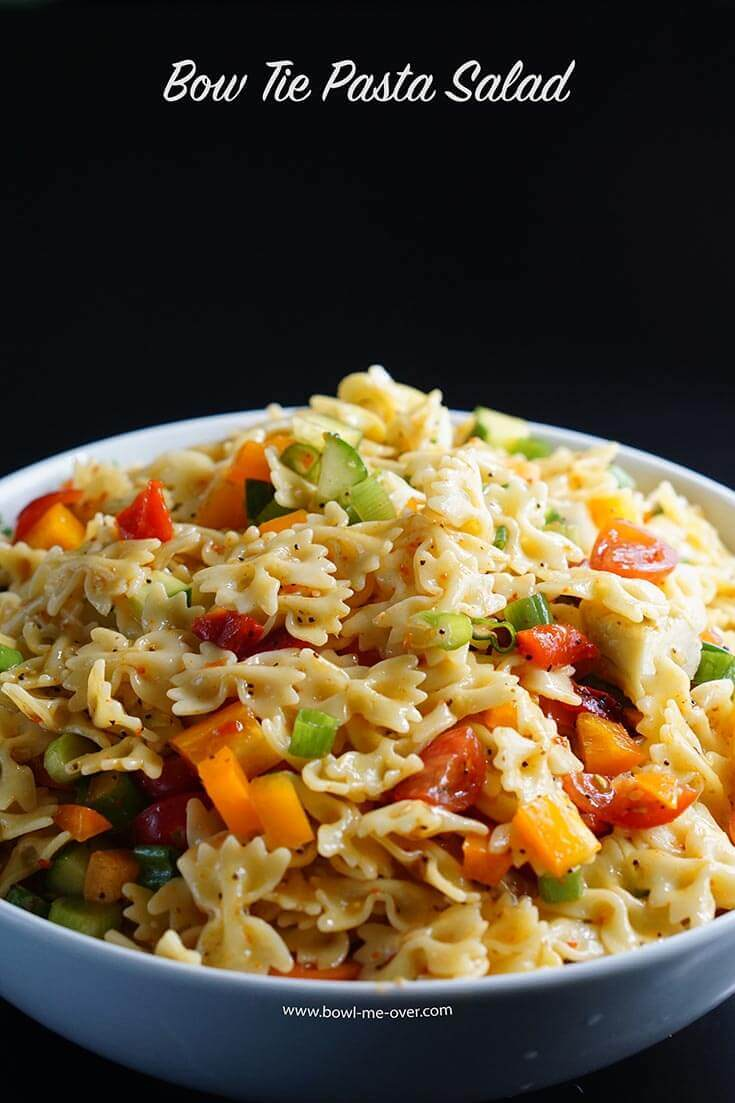 Bow Tie Pasta Salad Recipes - A white bowl filled to the brim with pasta salad filled with fresh vegetables and a great Italian dressing.