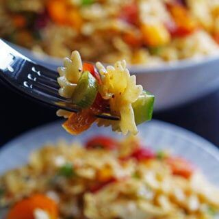 Bow Tie Pasta Salad Recipes - a close-up of a fork full of pasta salad. In the background is a white plate and huge bowl, each filled with salad.