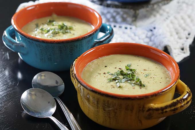 Two bowls of creamy zucchini soup recipe topped with shredded basil and fresh cracked pepper.