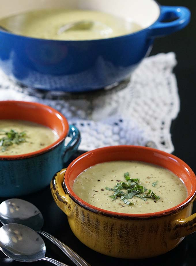Two bowls of creamy zucchini soup in bowls with spoons