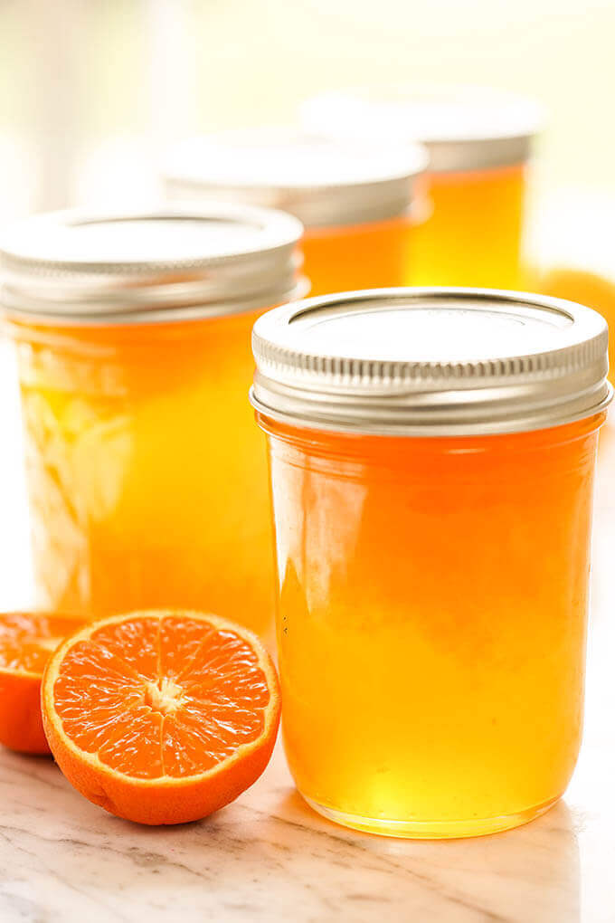 Jars of Mandarin Orange Jelly with fresh mandarins.