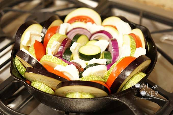 Sliced raw vegetables with cheese in cast iron skillet