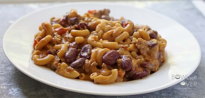 Tomato pasta on plate sitting on table.