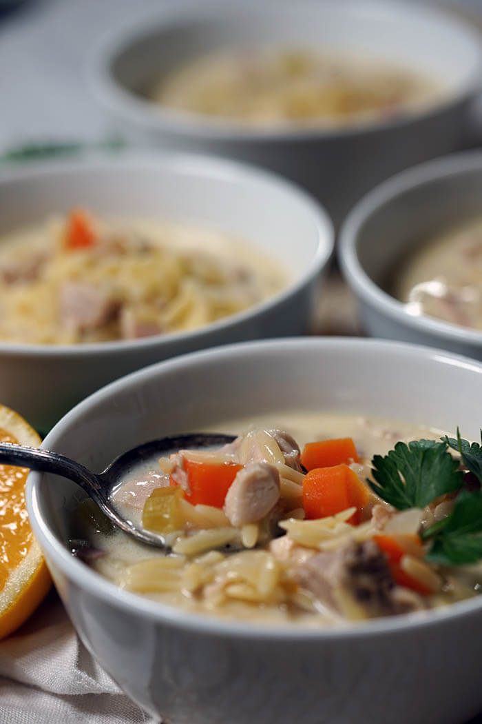 A bowlful of Lemon Chicken Orzo Soup with a spoon getting ready to dunk a big spoonful out to enjoy!