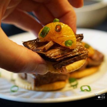 A Ritz Cracker topped with roast beef, a mandarin slice and sprinkled with green onions