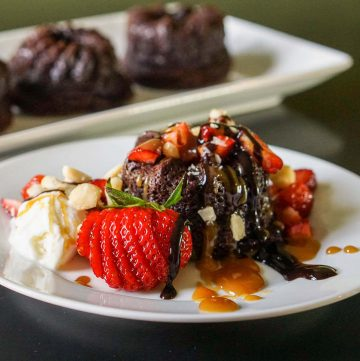 Chocolate Brownie Bundt Cake topped with ice cream, nuts and strawberries.