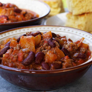 A close-up picture of a bowl of squash chili with a serving of cornbread.