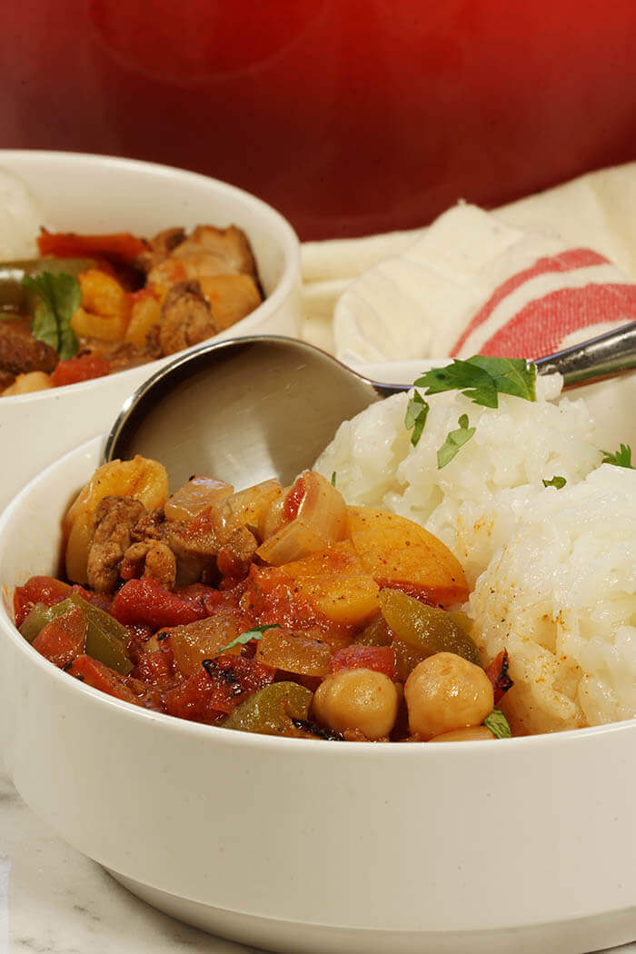 Two white bowls filled with spicy Moroccan Chicken Stew. Each meal comes with a side of white rice.