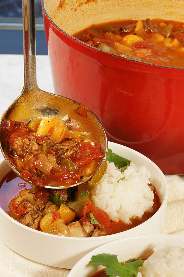 A red pot full of moroccan chicken stew. There's a ladle dishing up stew into a white bowl. The meal is served with white rice.
