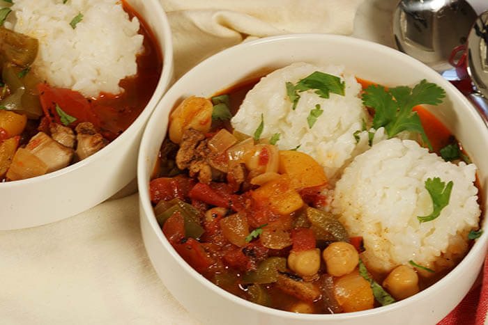 Two white bowls filled with stew. Each bowl has two dollops of rice and the stew is served alongside. The meal is garnished with chopped cilantro.