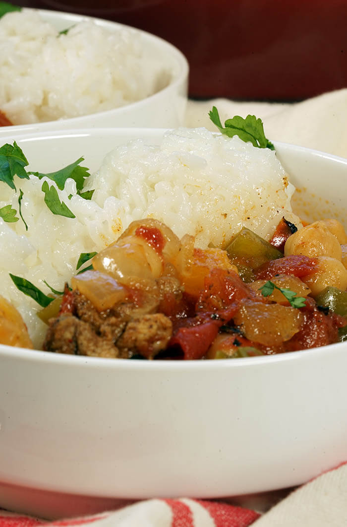 A white bowl filled with Moroccan Chicken Stew served with a side of rice. The meal is garnished with minced cilantro.