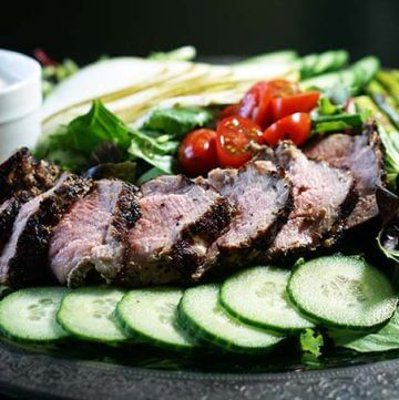 Grilled pork tenderloin salad with vegetables on silver platter.
