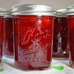 Clear jars of jam filled with a strawberry preserves recipe are lined up on a white towel and the jars are sealed.