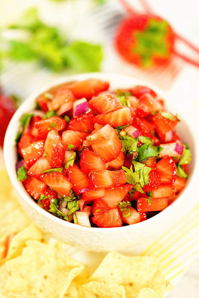 Strawberry Salsa in a white bowl surrounded by chips and fresh berries!