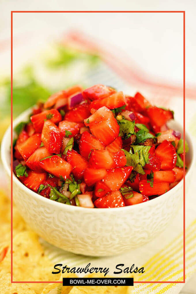 A white bowl filled iwith strawberry salsa surrounded by chips