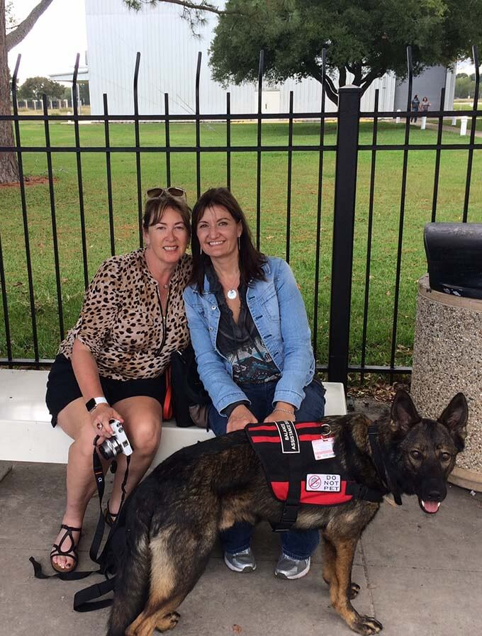 A picture of Deb and her friend Nicole with her service dog Shadow at the Houston Space Center in Texas.