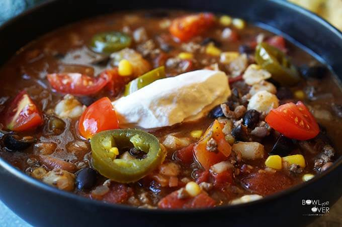 An easy recipe for taco soup in a black bowl topped with diced tomatoes, sour cream and sliced jalapeños