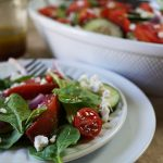 Cucumber Tomato Salad Recipe - a scattering of tomatoes, cucumber and bright fresh arugula is piled high on a white plate. The salad is dressed with an easy vinaigrette.