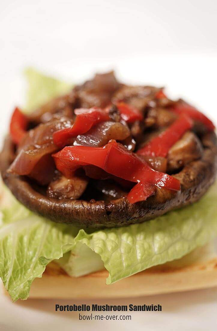 A burger bun topped with lettuce, portobello mushroom, onions and peppers in barbecue sauce.