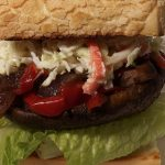A burger bun topped with lettuce, portobello mushroom, onions and peppers. Coleslaw toped off the sandwich, finished with a big hearty burger bun.