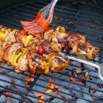 BBQ Chicken on hot coal grill basted with sauce.