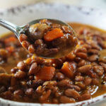 A bowl of vegetable bean soup with a spoon scooping out a serving!