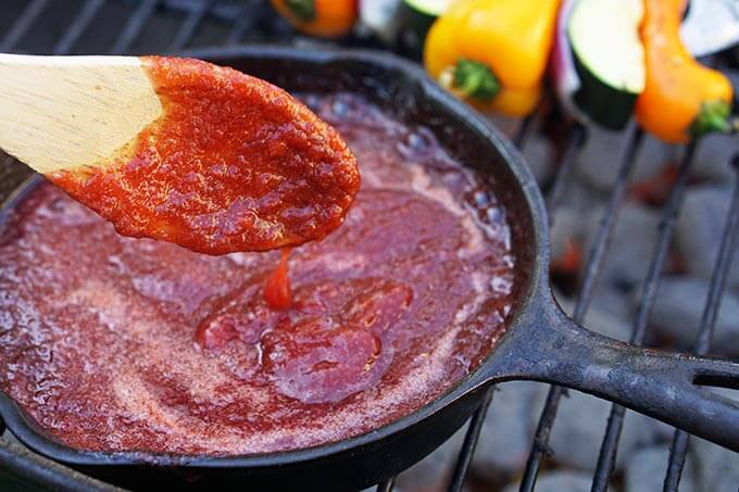 BBQ Sauce in skillet on grill with spoon.
