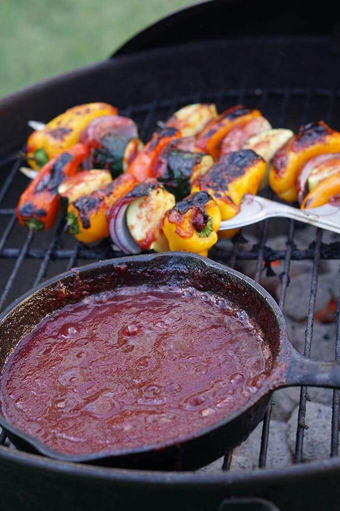 Plumb BBQ Sauce in cast iron skillet on grill with kabobs