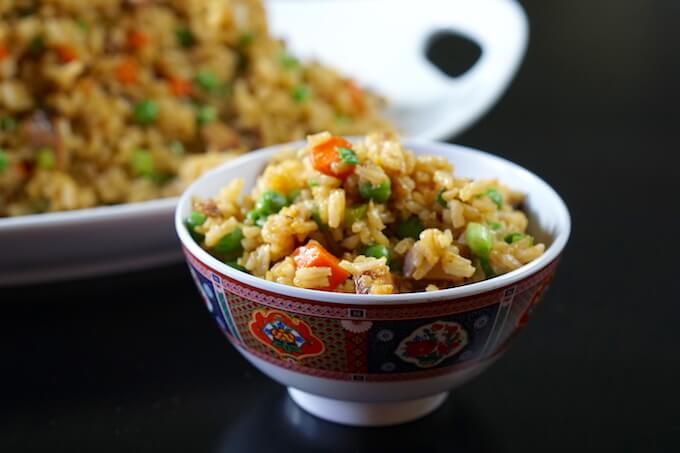 Easy Chicken Fried Rice Recipe in a small bowl on a black tabletop.