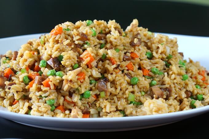 A platter of chicken fried rice recipe on a black tabletop.