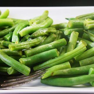 Steamed green beans on a white platter sitting on a black table.