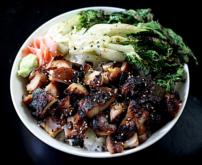 Teriyaki chicken bowl with grilled chicken and bok choy served over white rice in a big white bowl.