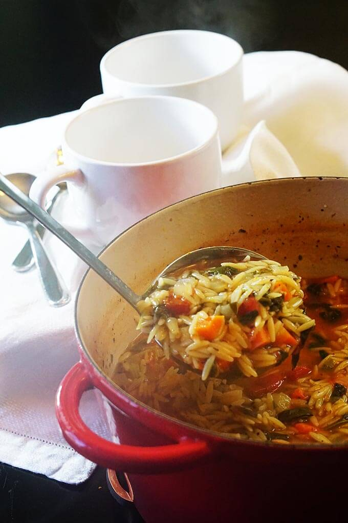 A red pot filled with orzo soup. There's a ladle scooping out a big helping and bowls standing by for serving!