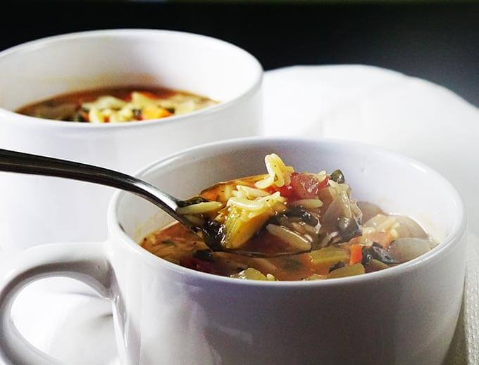 A white bowl filled with soup. There's a spoon serving up a healthy meal of vegetable orzo soup