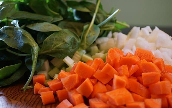 Chopped spinach, carrots and onions on a wooden cutting board.
