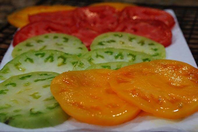 A platter of sliced tomatoes. There are several different varieties, orange, red and green tomatoes.