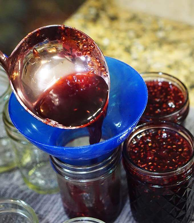 Homemade jam being ladled into jars.