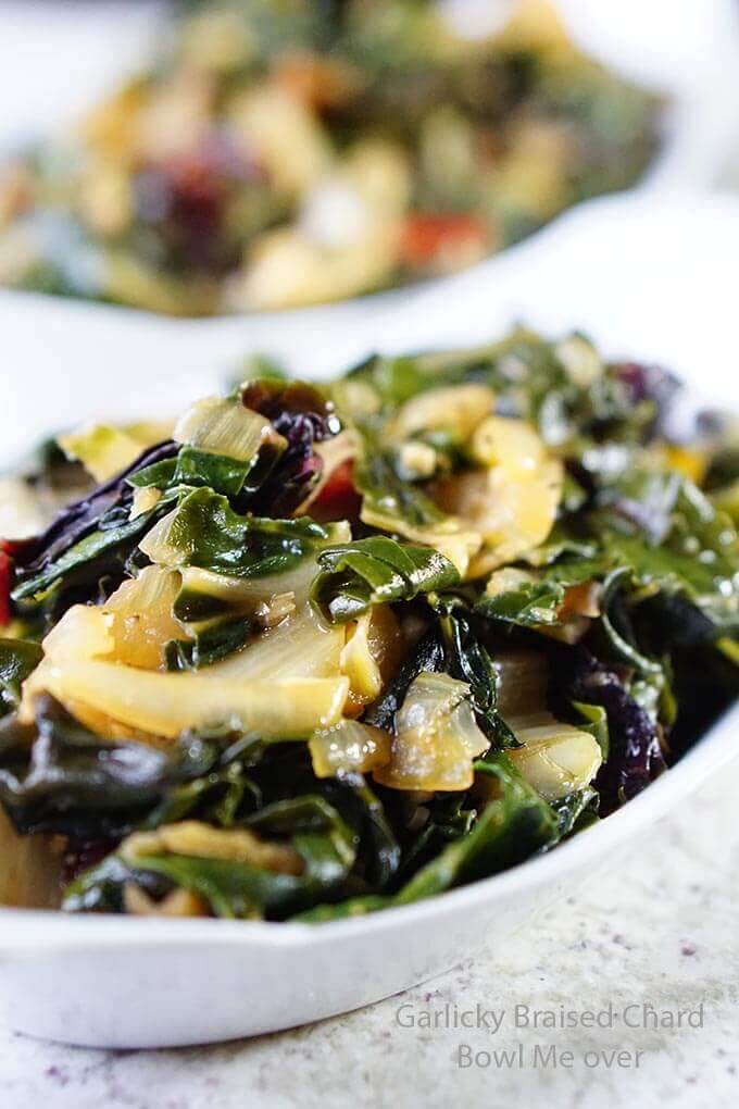 braised chard in a white bowl on a marble countertop